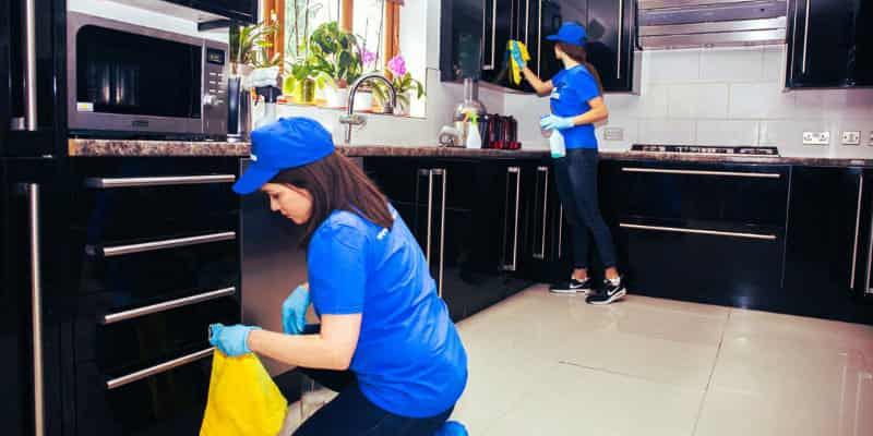 two girls in blue wiping kitchen cabinets