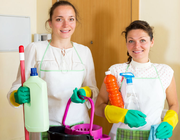 two ladies standing with bucket and bottles in hand