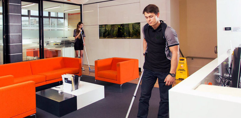 man and woman with mops scrubbing office floor