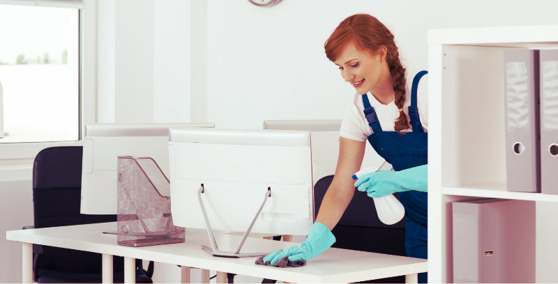 lady with spray bottle in hand wiping office desk