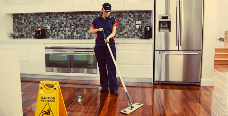 lady in blue dress wiping hardwood floor