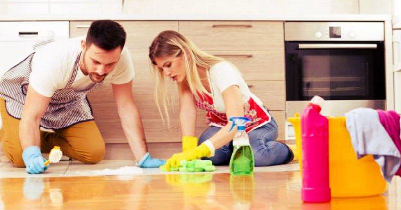 man and woman scrubbing hardwood floor