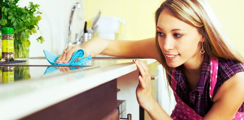 girl in pink wiping the counter with blue cloth