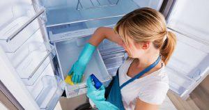 happy woman wiping refrigerator