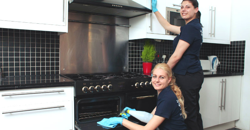 two women in black uniform wiping kitchen chimney and oven