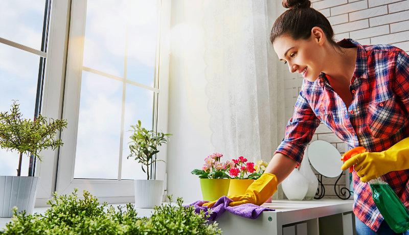 beautiful young woman wiping kitchen counter