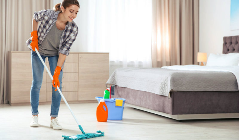 beautiful young woman happily mopping the bedroom floor