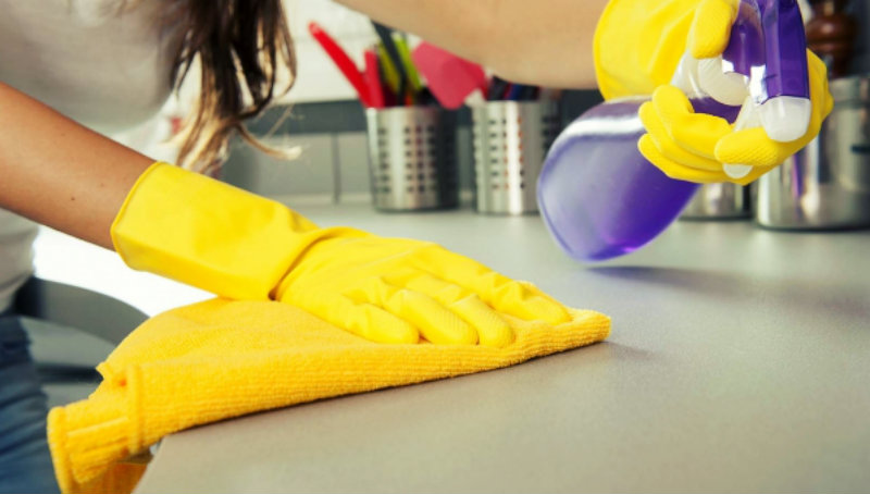cropped image of a woman wiping kitchen counter
