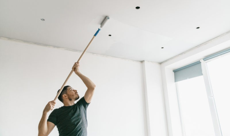 a young man dusting his roof with a dusting stick
