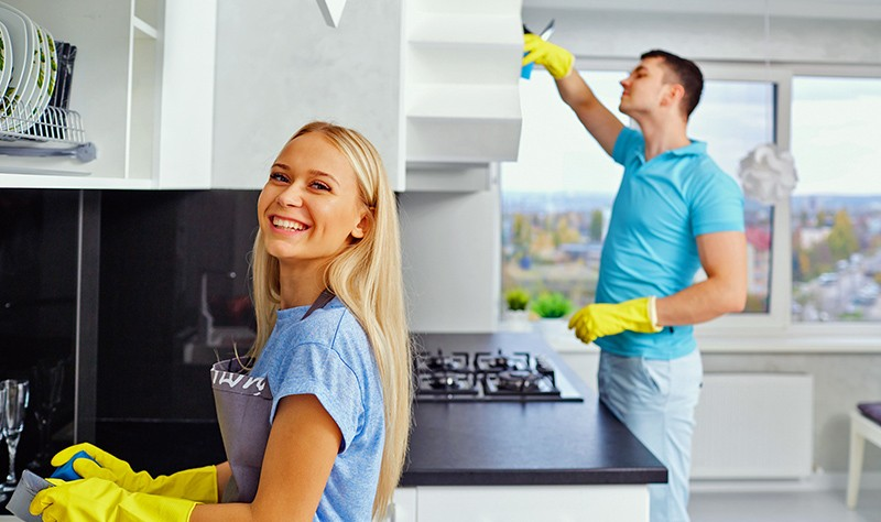 a couple in a kitchen wearing yellow gloves