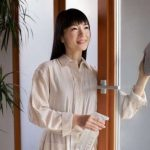 Marie Kondo wiping the window glass with a cloth rag