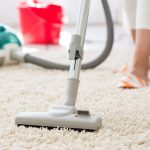 cropped image of a woman vacuuming a carpet