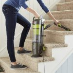cropped image of a young woman vacuuming the carpeted stairs