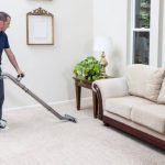 young man vacuuming the carpet