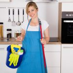woman standing in a kitchen with a wiper and a bucket
