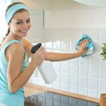 young woman wiping kitchen tiles with a cloth wipe
