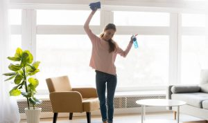 young happy woman dancing and holding a spray bottle and a cloth mop