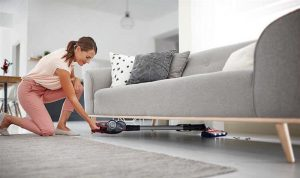 young woman vacuuming hard to reach places