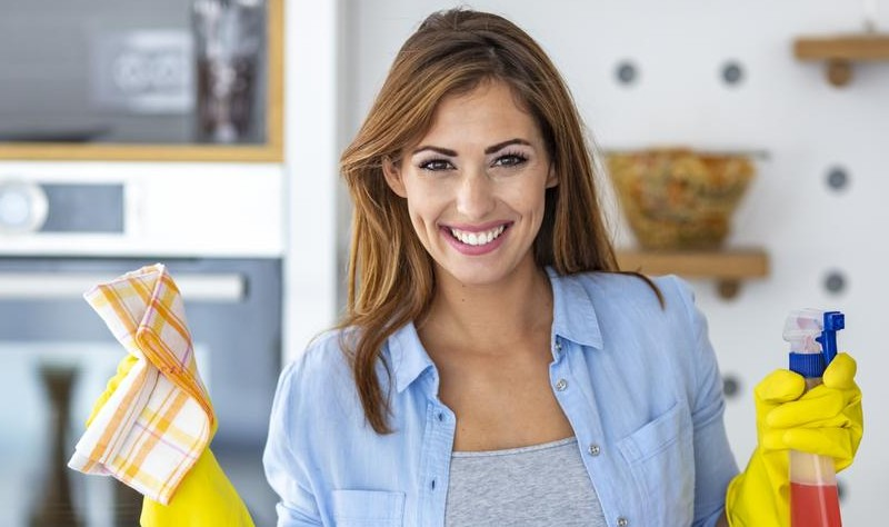 young woman holding a cloth mop and spray bottle in her hands
