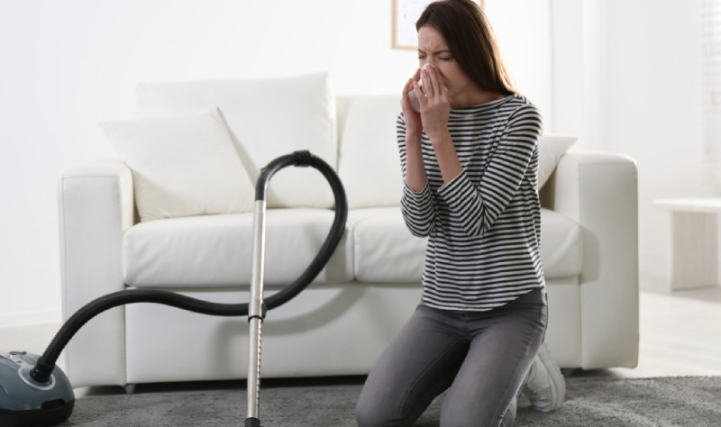 young woman sneezing while vacuuming her house