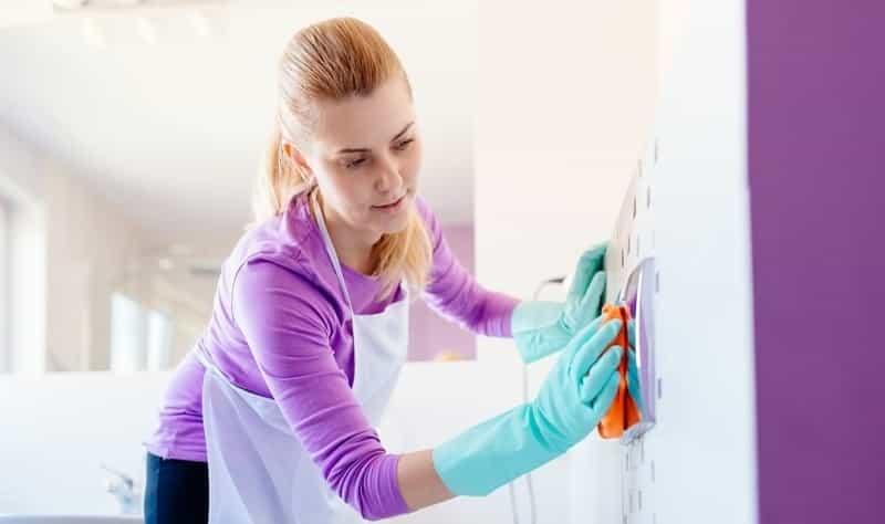 young woman disinfecting a surface