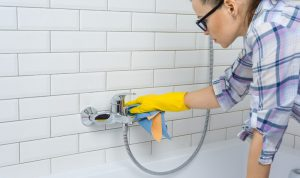 young woman wearing eye glasses wiping a shower jet with a cloth