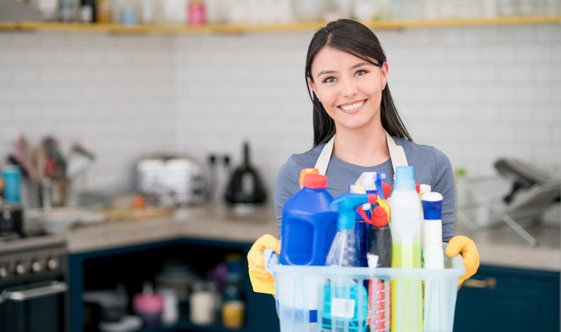 young woman holding a bucket full of chemical bottles and spray bottles