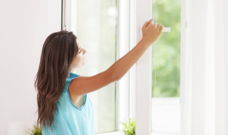young woman opening a window and enjoying the fresh air