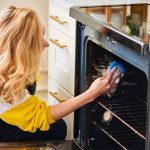 woman with blonde hair wiping an oven