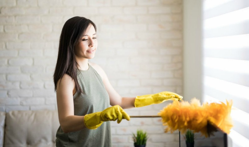 young woman dusting her house